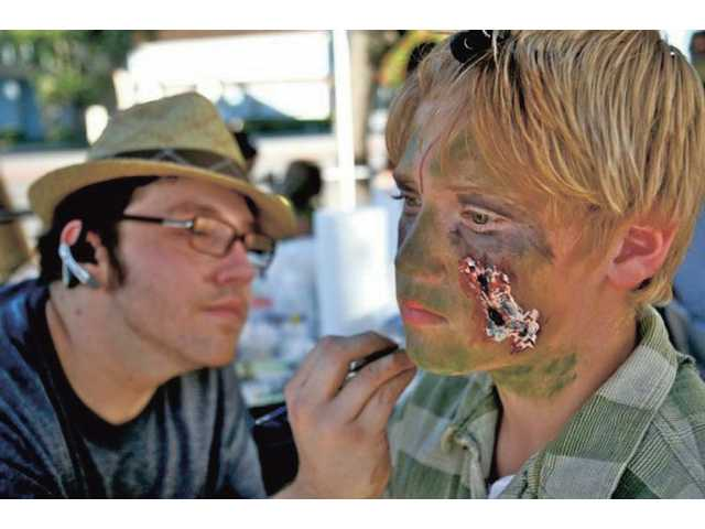 George Kritikos, left, of Studio Makeup Academy, helps 13-year-old Bryce Youngquist transform into a zombie outside Brave New World in Newhall on Saturday. Over 500 participants made either monetary donations or gave canned food to benefit the Santa Clarita Valley Food Pantry.