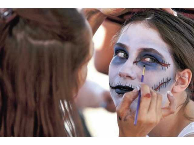 Brandy Sims, left, of Studio Makeup Academy, applies makeup to Rhiannon Walsh outside Brave New World comic store.