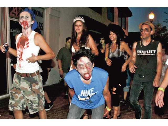 Zombies make their way down Main Street in Downtown Newhall toward William S. Hart Park on Saturday.