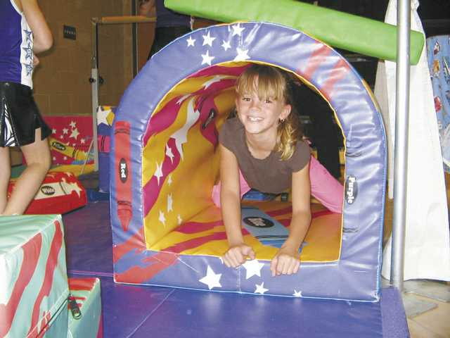 Amanda Parrish climbs through a tunnel set up by Gymnastics Unlimited at the sixth annual Kid Expo in Canyon Country on Sunday.