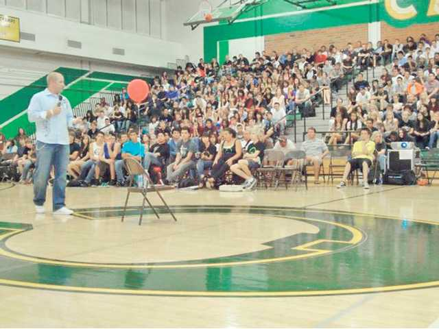 Sarich speaks during the assembly in the Canyon High School gym.