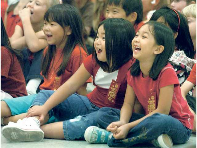 "Azriel Manalaysay, right, and  Ivy Kim laugh alongside their second-grade classmates as ""Retro Bill"" presents serious life lessons in a humorous way at Rancho Pico Elementary school on Tuesday."