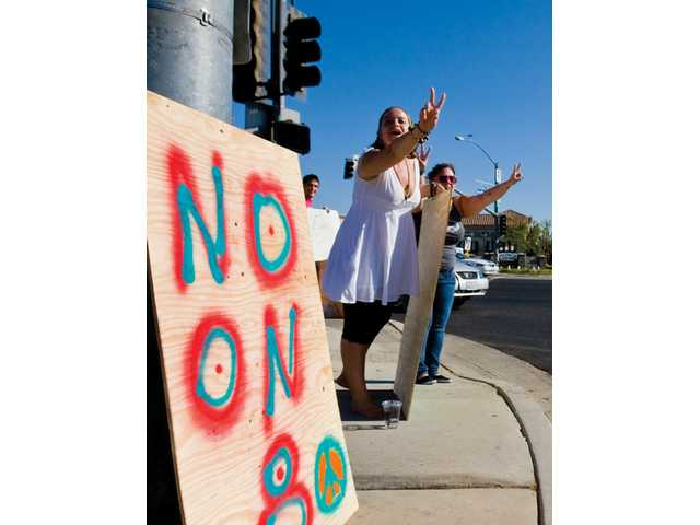 Left to right: Tai Farnsworth and Chynna Dolye stand at the corner of McBean and Valencia Boulevard in opposition to Proposition 8 on Monday afternoon. The two were joined by eight other protesters, and were both cheered and scolded by motorists at the busy intersection.