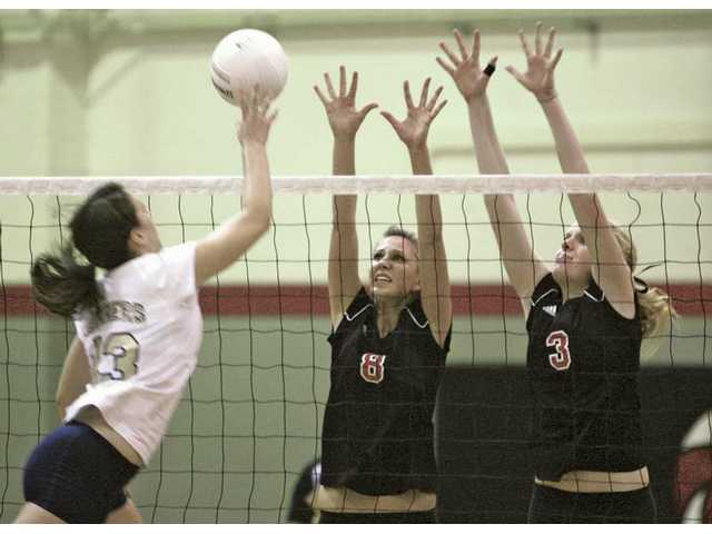 Hart High volleyball players Jennie Long (8) and Breena Beckett (3) rise to block the shot of West Ranch's Allison Summers Tuesday at Hart High School. The Indians won the match 3-2.