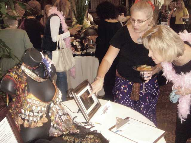 "Donna Kreutz, right, gets a taste of tribal elegance from Sally Archer Clifton. Clifton joined Wendy Heffernan and Jacqui Alomia in donating the ""American Tribal"" bra."