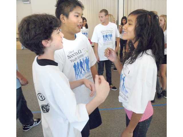 Student Michael Fleischmann, left, of Rio Norte Junior High School meets Tyler Tran and Damaris Herrera of Castaic Middle School as they participate in an activity.