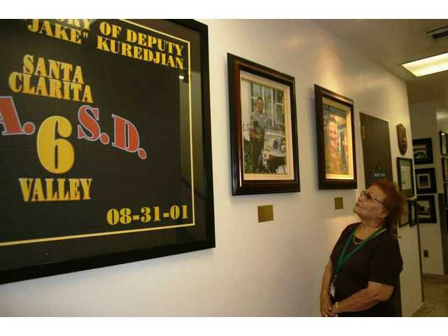 "Estelle Foley, the SCV Sheriff's Station's historian for a quarter-century as of Oct. 23, 2008, shows visitors the part of the hallway dedicated to Deputy Hagop ""Jake"" Kuredjian, killed in the line of duty in August 2001."
