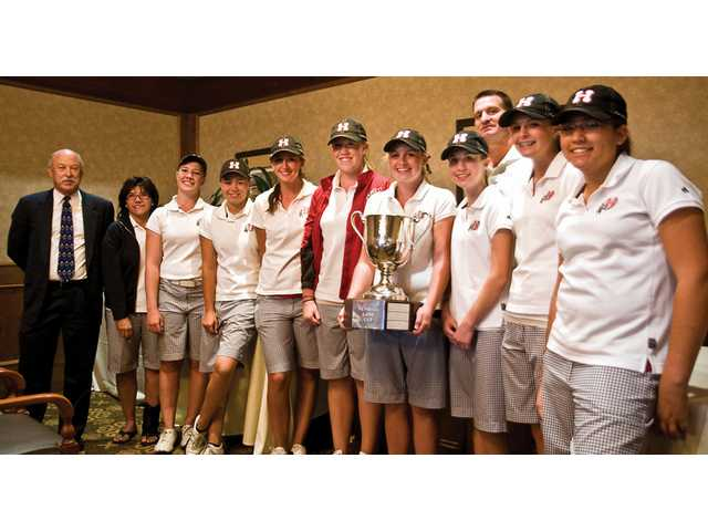 The Hart High School girls golf team, which won back-to-back Newhall Cup titles, stands with the team championship trophy on Wednesday at The Tournament Players Club in Valencia.