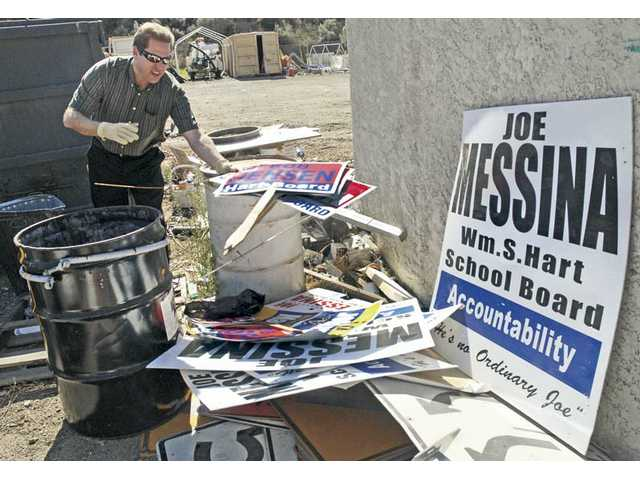 City of Santa Clarita Supervising Community Preservation Officer Curtis Williams tosses a stack of campaign signs into a pile at a city storage yard in Saugus on Thursday. The signs were removed from places where they were illegally displayed on public property.