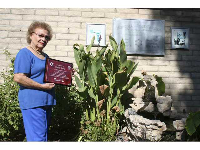 Near the fountain in the Memorial Garden she helped create at the Santa Clarita Valley Sheriff's Station in 2002 to honor fallen deputies, Estelle Foley holds the special plaque her co-workers gave her to mark 25 years as the station's volunteer historian.