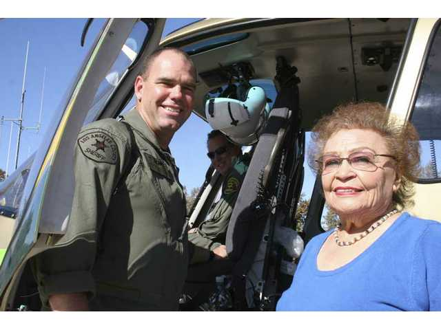 Dep. Dale Ryken, observer with the SCV Sheriff's Station helicopter crew, gets ready to buckle Estelle Foley, station historian, into the back seat for her first flight, piloted by Dep. Eric Allen (background).