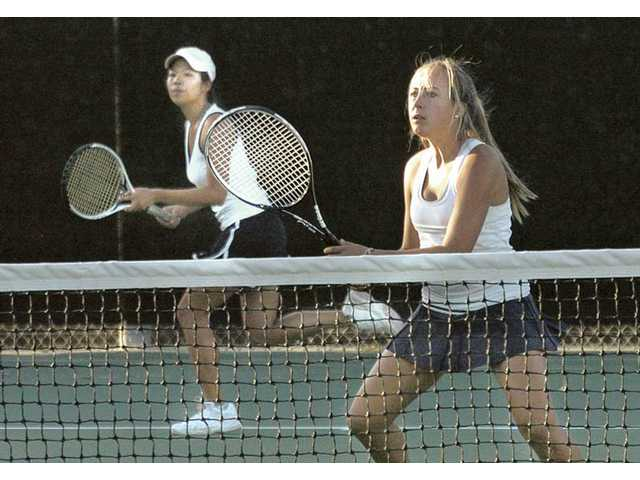 West Ranch's Lena Poonnapatam, left, and doubles teammate Salene Scamardo anticipate the tennis ball at West Ranch High Thursday.