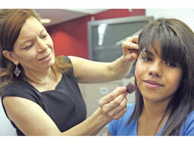 Ivet Silva, of Academy of Esthetics and Cosmetology, applies a scar on Bowman High School student Brenda Briseno, 17, Friday afternoon during the school's Career Day event.
