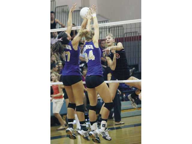 Viking players Katie Hank (18) and Christina Worth (3) rise to block a ball during Valencia's three-game sweep at Hart High on Thursday afternoon.