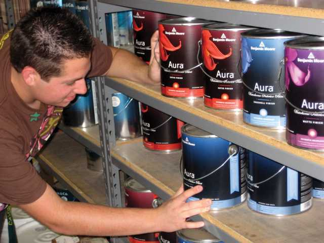 Brandon Dell'Olio examines a gallon of Aura paint at Sand Canyon Paint & Hardware in Canyon Country. Aura is a low-VOC paint that is more health-conscious and environmentally friendly than standard oil-based paint.