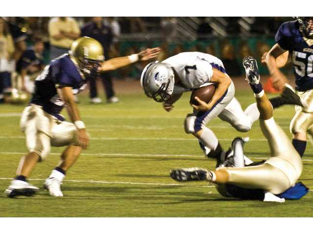 Saugus High School's Kollin Depew steam rolls West Ranch High'sTrent Yokofich and Frankie Madero in the second quarter.