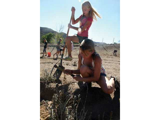 Eleven-year-old friends Christina Ewart, top, and Sophia McLaren-Cobb help remove weeds at Carousel Ranch Saturday as part of Make a Difference Day. More than 3 million people participated nationwide last year.