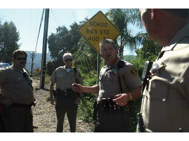 Sheriff's Deputy Artie Thompson, assistant coordinator for the Reserve Deputy Program, talks with his reserve deputies outside the possible residence of a sexual predator near a school bus stop in Canyon Country Saturday afternoon.