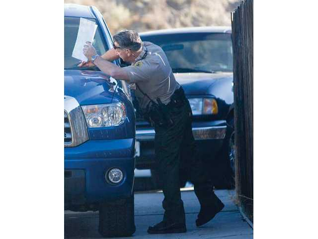 Reserve Deputy Schiro makes sure the Vehicle Identification Number matches the records of a registered Canyon Country sex offender Saturday morning. Around 230 sex offenders call the Santa Clarita Valley their home.