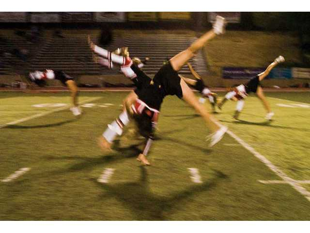 The Hart High varisty cheer squad tumbles down the center of the field during halftime at a game played Oct. 3.