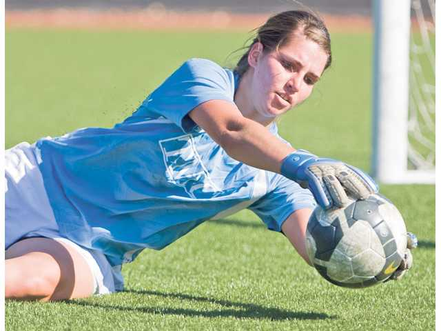 The Master's College freshman goalkeeper Kayla Jones dives to her left to make a save during the Mustangs' practice Thursday afternoon at TMC.