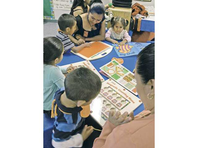 Felicitas Vargas, top center, plays learning games with son Oscar, 4, and daughter Brenda, 2. Local educators and parents are worried federal leaders will cut funding for the literacy program due to a lack of hard data proving the program is effective.