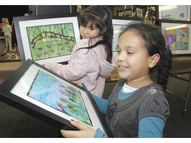 In this Oct. 13 photo, Sonia Flores, 8, right, and Myriam Castillo, 6, display their artwork at the Kids Art Fair at Live Oak Elementary School. The school adopted the Kids Art Fair program - designed to elevate the importance of creative, artistic expression in a child's development - in 2007. It was the school's first art fair.