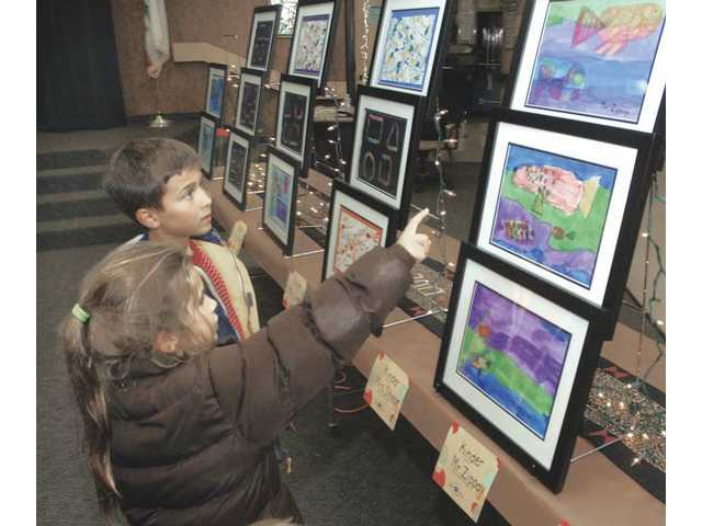J.T. Yeyna, 8, and sister Charlianne, 6, examine the work of their kindergarten schoolmates.