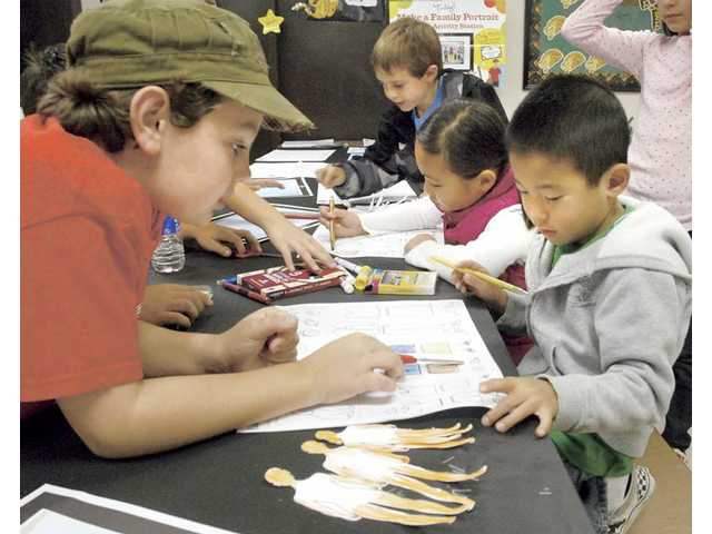 Fifth-grader Liam Johnson, left, helps Caleb Cho, 5, as he creates a portrait of his family.