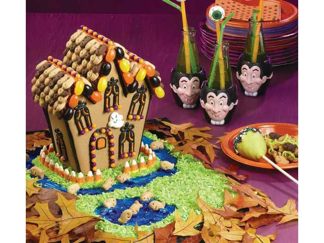 "Happy Haunted House        Wilton Halloween Cookie House Kit        10 x 14-inch cake board        Cornstarch        Pepperidge Farm Cinnamon, Chocolate and Honey Goldfish Grahams        Wilton Piping Gel        Wilton Royal Blue and         Kelly Green Icing         Colors        Flaked coconut        Candy cornPrepare icing mixes following instructions. Attach house to cake board. Outline door with black icing; attach candy dots. Outline door window in black icing; fill in with orange icing and smooth with finger dipped in cornstarch.Outline windows with black icing; add orange icing accents. Attach candy dot window sills.Spatula ice roof; attach crackers to roof with dots of icing. Decorate house eaves with jelly beans attached with dots of icing. Add orange outline to roof peaks; attach candy dots.Tint portion of piping gel blue; spatula blue gel ""moat"" and ""pond"" on cake board; arrange crackers in the water. Brush clear piping gel onto open areas of cake board; sprinkle with green-tinted coconut. Arrange candy corn around house with dots of icing."
