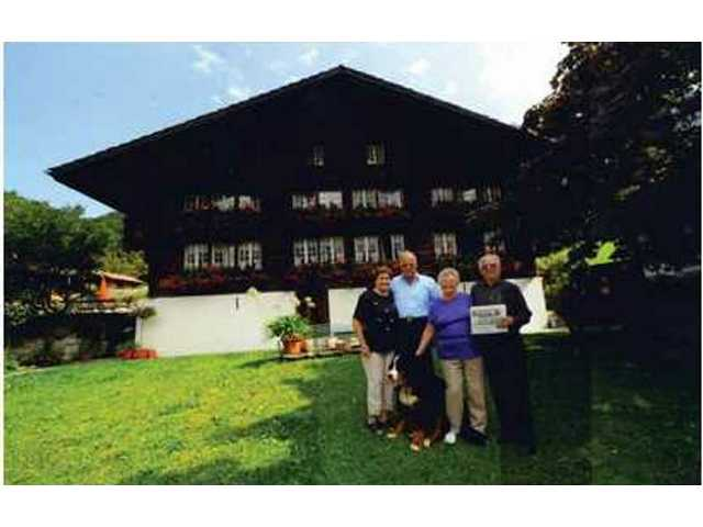 Skip and Sandy Hasler, 47-year residents of Saugus, holding The Signal of Sept. 2 in front of the Hasler Ancestral Home (circa 1820s) at Gsteigwiler, Switzerland in the Bernese Oberland Region of the Swiss Alps. To the left are relatives and 5th generation owners of the home, General Heinz Hasler, retired Chief of the General Staff of the Swiss Armed Forces and his wife Edith with their Bernese farm dog, Nico.