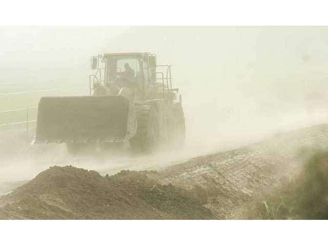 A tractor is engulfed in a cloud of dust pushed by high winds as it moves along a dirt road near Hasley Canyon Road in Castaic Tuesday afternoon. A Santa Clarita Valley high wind warning remains in effect until 6 a.m. Wednesday.