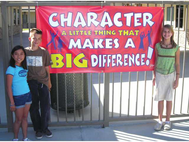 Lea Saet, left, Tyler Cole and Megan Hubbard, right, show off their character sign at Fair Oaks Ranch Community School