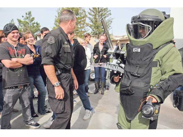 U.S. History teacher Marcy Calnan, far right, wears a 90-pound suit and 20-pound helmet, used by the Los Angeles County Bomb Squad, during a presentation at Valencia High School Tuesday morning.