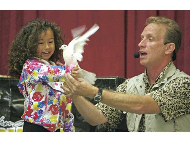 Paige Goodwin, kindergartner at Santa Clarita Elementary School, left, assists John Abrams in performing magic tricks during an afternoon presentation Tuesday. Abrams performed magic tricks with different animals.