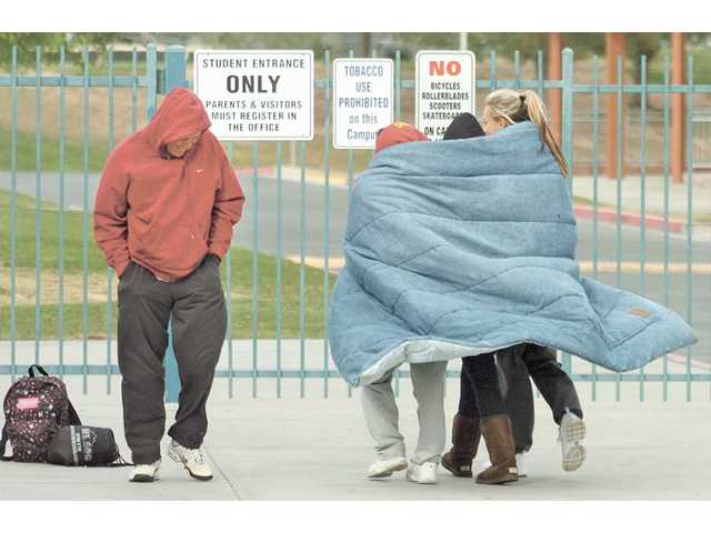An unidentified man passes three girls as they shelter themselves from a chilly wind while walking to a tennis match between Valencia and Hart High at Valencia High School on Tuesday.