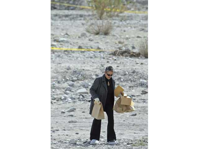 Toni Martinez, a homicide detective with the Los Angeles Sheriff's Department, carries bags of evidence from the crime scene Tuesday afternoon. A homeless man was stabbed to death Monday night in the Santa Clara River near the Soledad Shopping Center.