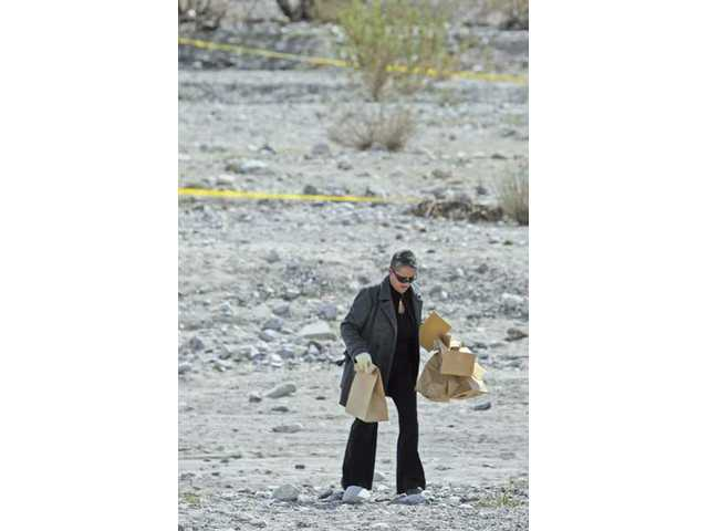 Los Angeles Sheriff's Department homicide Detective Toni Martinez carries bags of evidence from the crime scene where a homeless man was stabbed to death in the Santa Clara River in October.