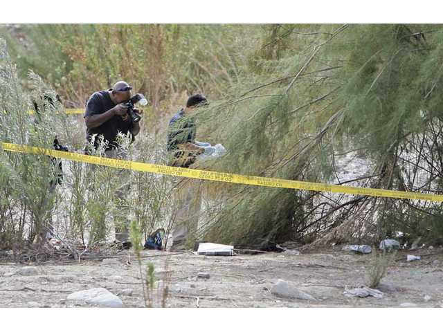Deputy Jeff Collins with Los Angeles County Sheriff's crime lab photographs the scene near the Santa Clara River where a man was stabbed to death Monday night.