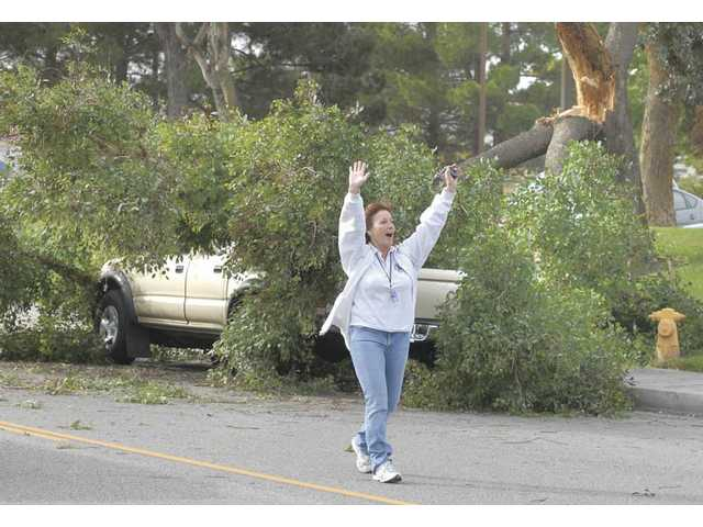Heidi Levy, who works at Bowman High School, directs traffic after a tree limb fell on a Toyota truck while its driver waited to turn right onto McBean Parkway from Creekside Road in front of the Valencia Post Office on Tuesday afternoon.