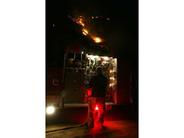 A firefighter from county Fire Station 126 tends to a fire engine Tuesday night in Val Verde, where crews made quick work of a three-acre blaze.