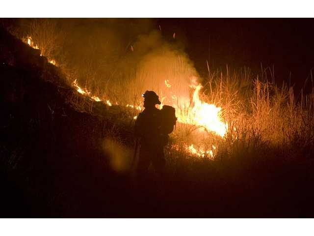 A firefighter battles a small blaze that broke out near Val Verde Park Tuesday night.