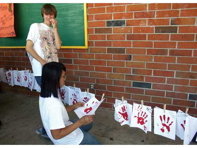 Juniors Daniel Craig, standing, and James Nguyen hang students' hand prints during the Red Hand Campaign event held Oct. 9 at Canyon High School.