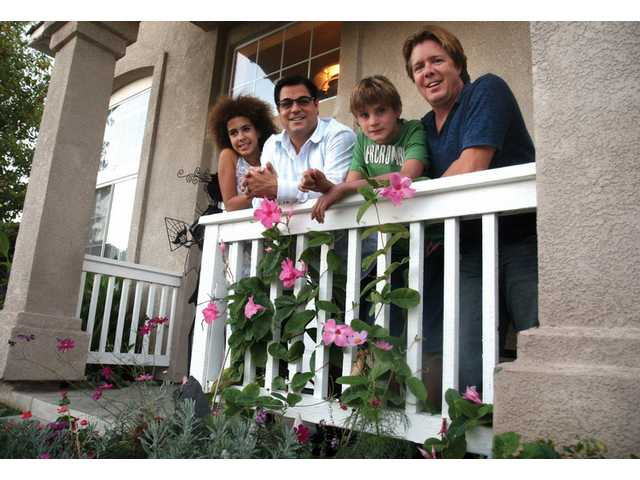 The Galluccio family — Madison, 11, Michael, Adam, 14, and Jon — pause on the porch of their  Stevenson Ranch home.