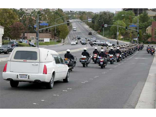The motorcycle escort and the hearse.