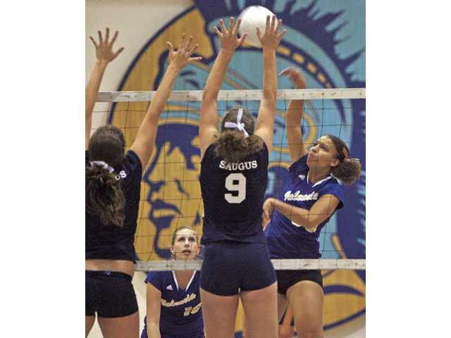 Valencia's Brianna Earley, right, spikes the volleyball as Saugus' Ashley Guthrie (9) tries to block Thursday at Saugus High.