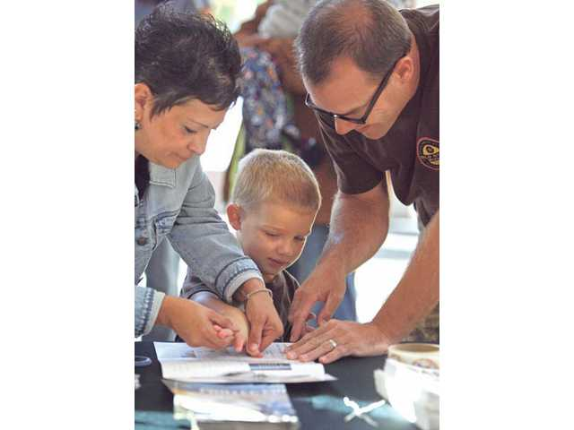 Chris Ward, left, representative for Assemblyman Cameron Smyth's office, helps Jason Knybel and his 3-year-old son Benjamin get fingerprints taken at the Westfield Valencia Town Center on Friday. The event provided parents with information on child safety.