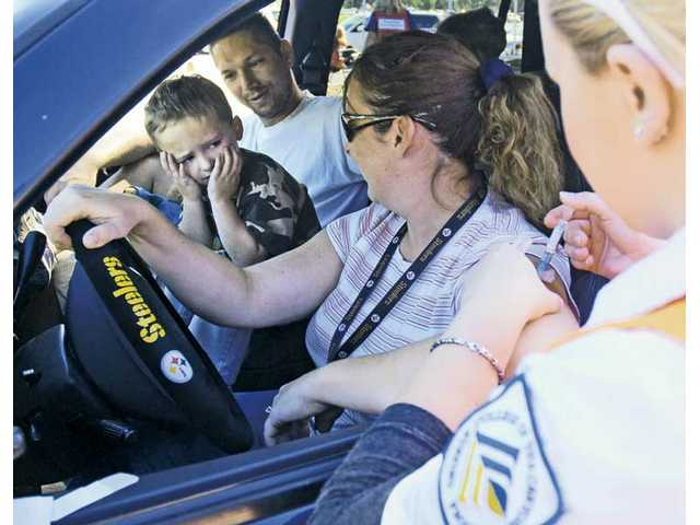 Three-year-old Logan Bruessel, of Canyon Country, left, hides his face as he sits between father Dennis and mother Lori while her flu shot is administered by College of the Canyons nursing student Dasha Khoudoiar, right, at the drive-through flu clinic held at the college.