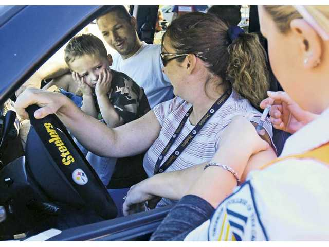 Logan Bruessel, 3, of Canyon Country, left, hides his face as he sits between father Dennis and mother Lori while she gets a flu shot from College of the Canyons nursing student Dasha Khoudoiar at the drive-through clinic held at COC on Friday.