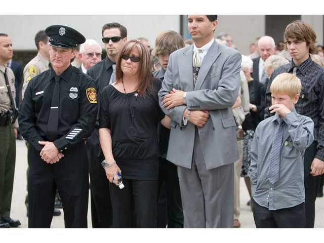 Family members and friendsof the late Deputy Randy Hamson, including brother Tim, Randy's wife Cindy and two young sons Nicholas and Joshua, watchas Hamsom's casket is placed inside the hearse after the funeral service at Grace Baptist Church in Saugus Thursday morning. Hamson was laid to rest at Eternal Valley Memorial Park and Mortuary.